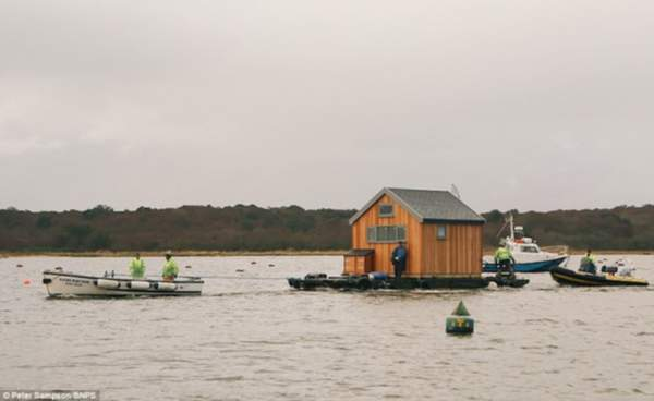 Meet the man who rented a boat, crane and dropped $67,000 to move one little hut